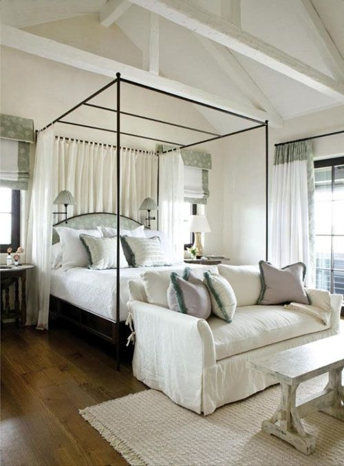 Beautiful iron upholstered canopy bed with curtains at back and sconces bedroom apartment images 08